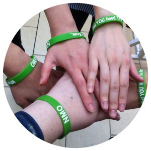 A huddle of five hands, each wearing a green NMO awareness bracelet.